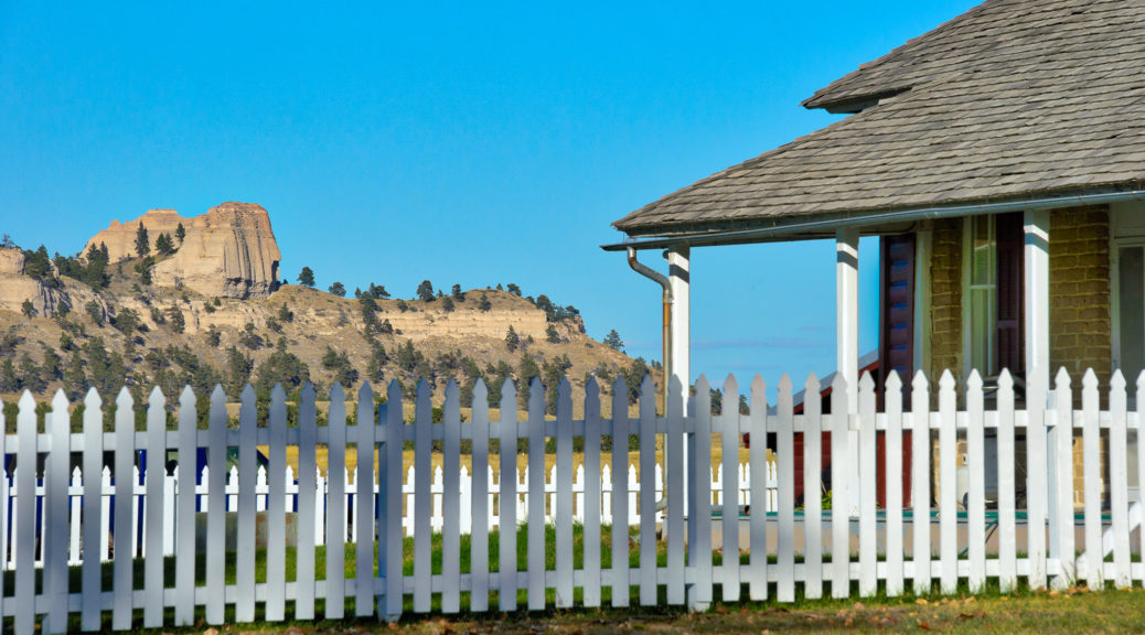 Red Cloud Buttes are visible over a picket fence behind one of the adobe officer's quarters in Fort Robinson State Park in Nebraska.