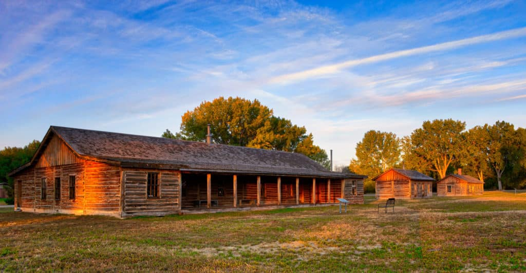 A re-creation of the Adjutant Building, the Cheyenne Outbreak Barracks, and the Guard House on the old parade ground catch the last rays of the autumn sun in Fort Robinson State Park, Nebraska.