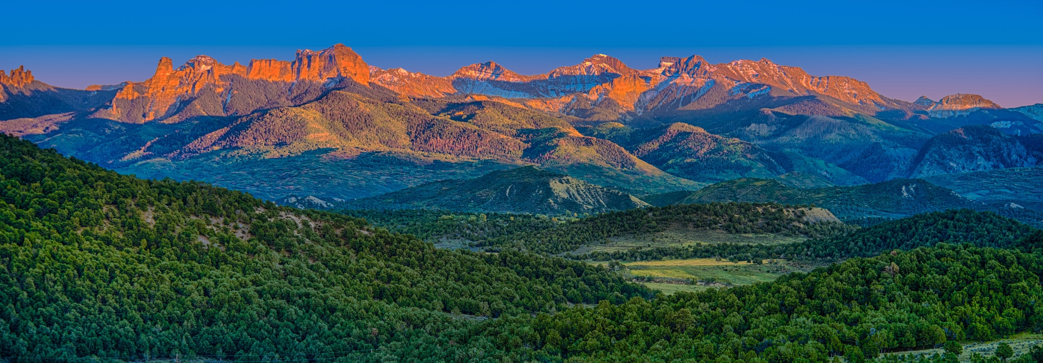 The last light o the days washes the Cimarron Mountains in orange and pink light as seen from Ridgway State Park outside Ridgway, Colorado.