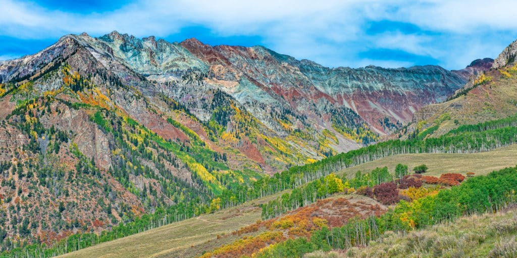 The highly mineralized rocks of the San Juan Mountains contrast with the bright fall colors of the Gambel oaks and aspen trees.