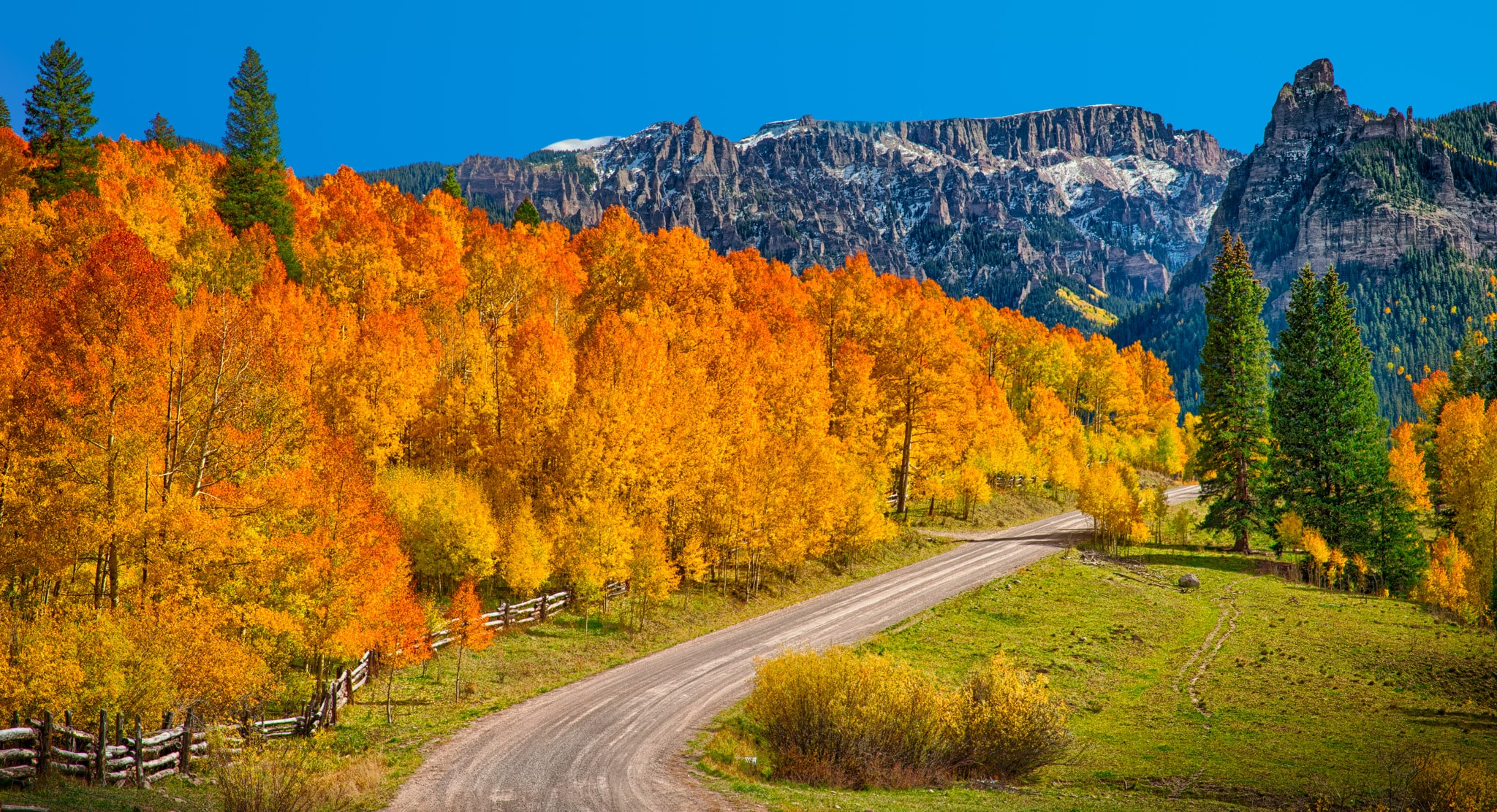 Flaming aspens and a log fence border Owl Creek Pass Road, heading toward the Cimarron Mountains near Silver Jack Reservoir between Ridgway and Cimarron, Colorado.