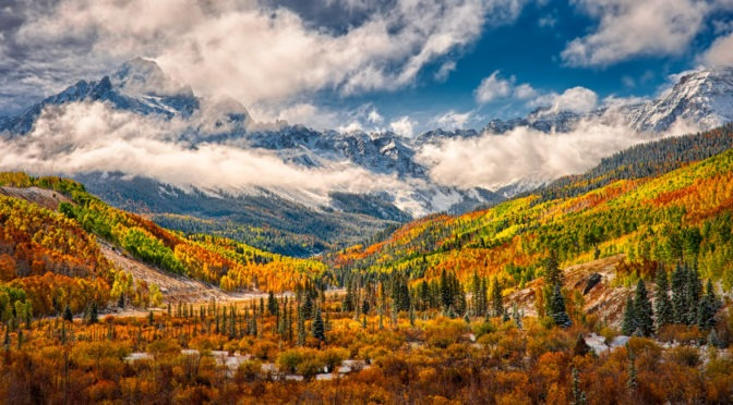 Colorful aspens and russet oaks treat the eye along CR 7 near Ridgway, Colorado, with the snow-capped mountains of the Sneffels Wilderness in the distance under retreating storm clouds.