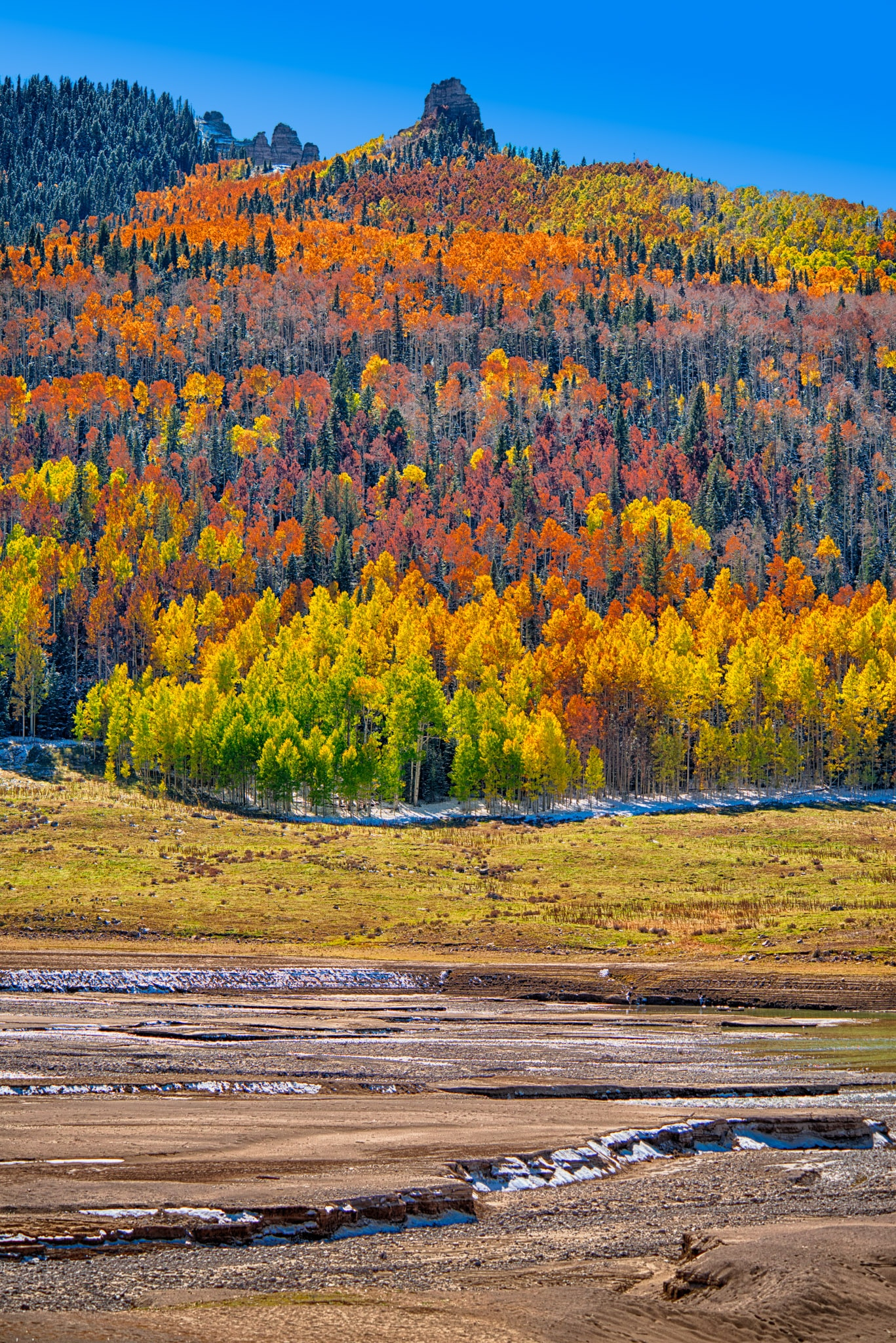 Green, yellow, orange, and red aspens march up the mountainsides above Silver Jack Reservoir on Owl Creek Pass Road near Ridgway, Colorado.