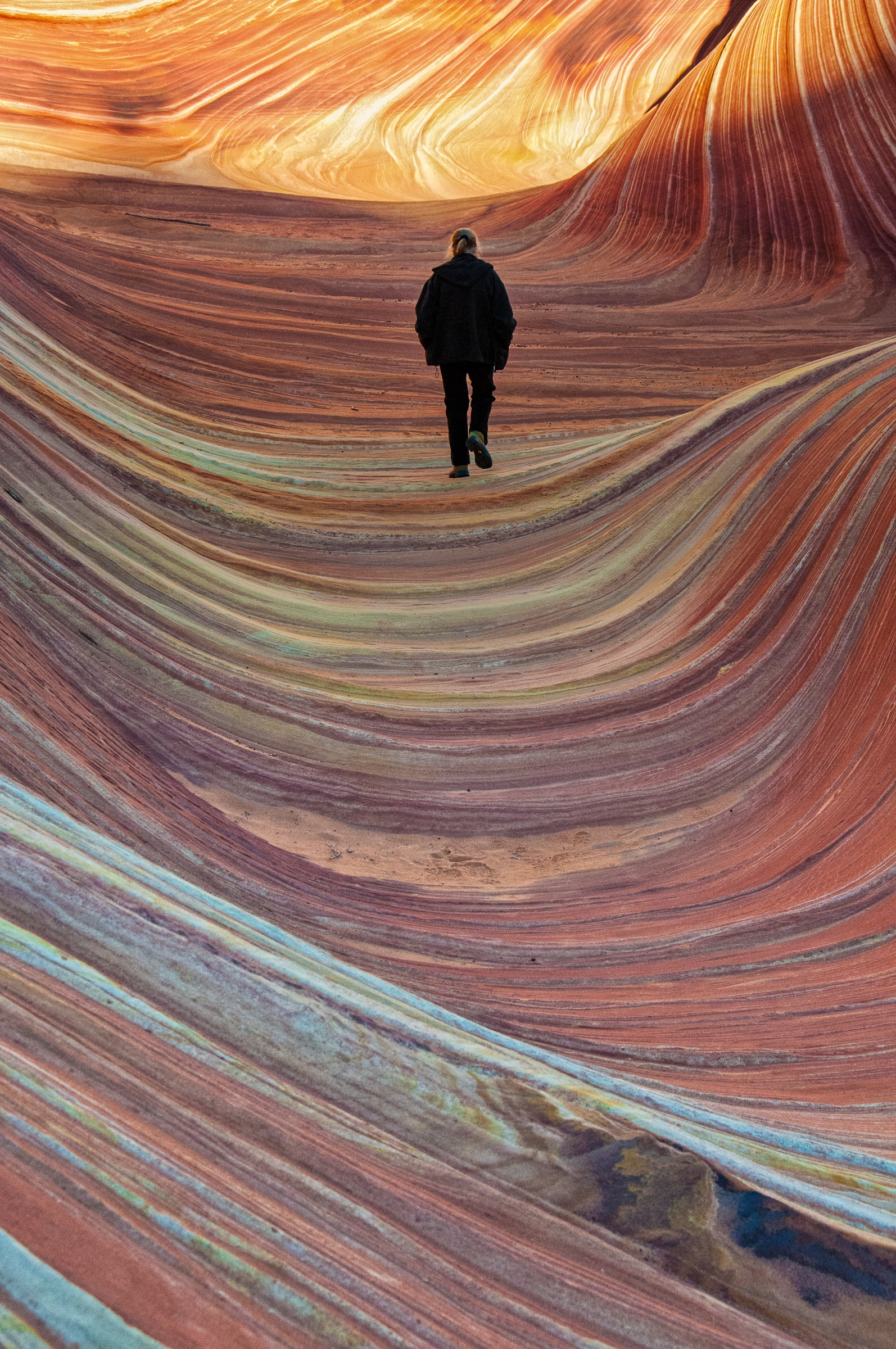 Woman walking through the Wave in the North Coyote Butte area of Vermillion CLiffs National Monument.