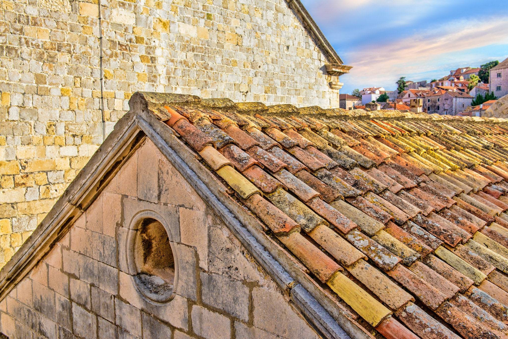 A red-tiled roof and pediment as seen from the city walls of Dubrovnik Old Town in Croatia.