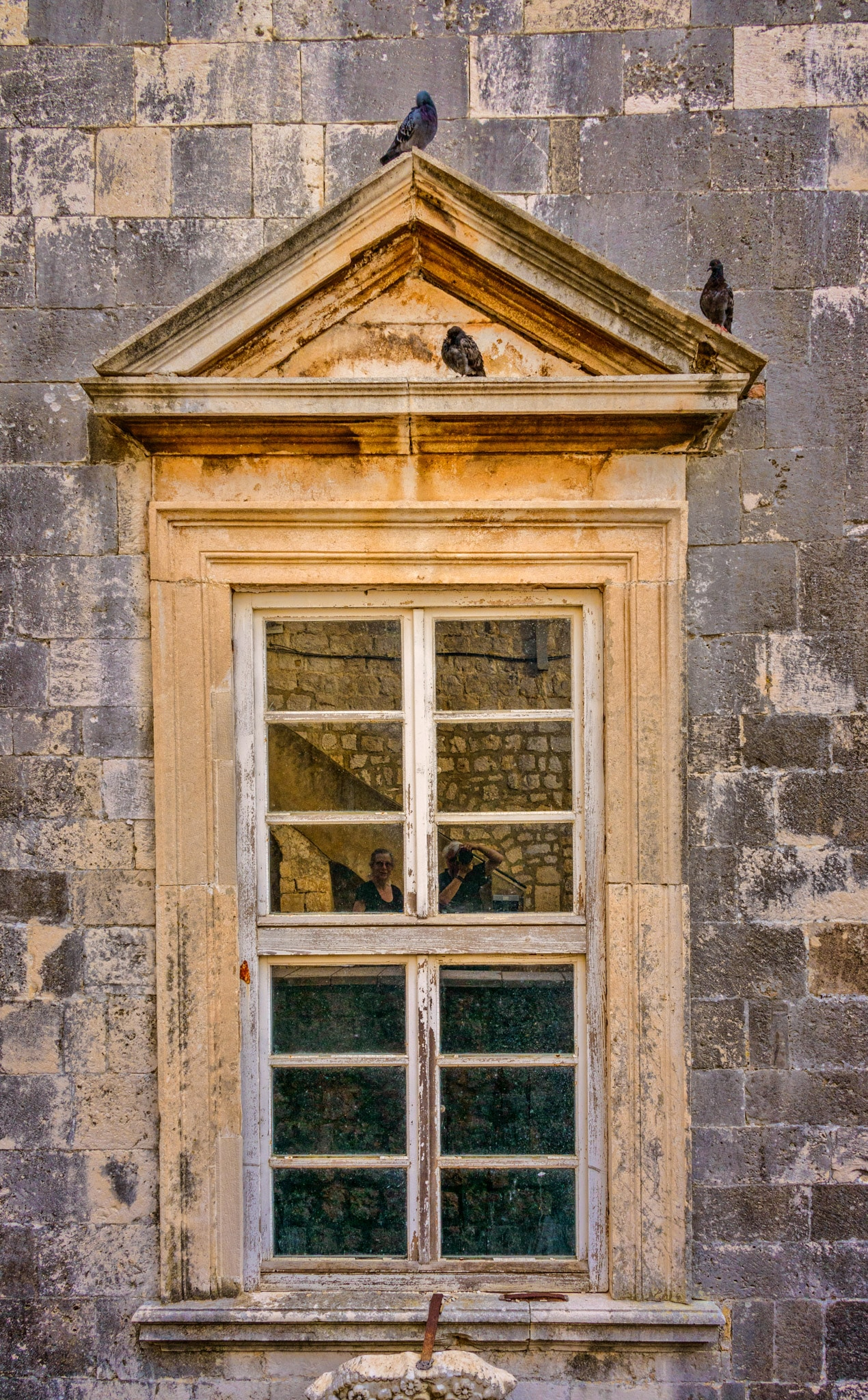 A window with a Roman-style peaked pediment as seen from the wall surrounding Dubrovnik Old City in Croatia.