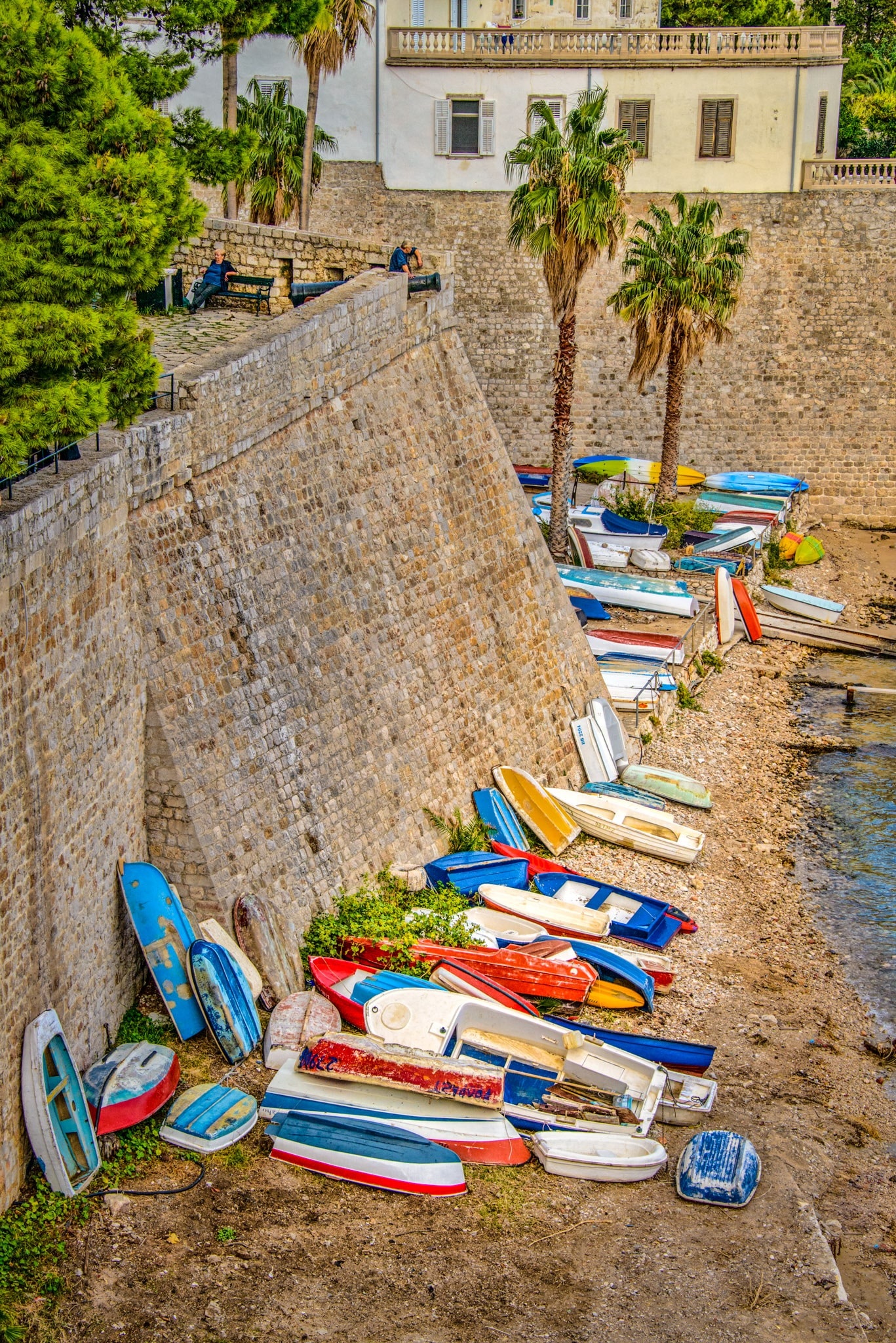 Colorful rowboats pulled onto shore against the Old Dubrovnik City walls in Croatia.