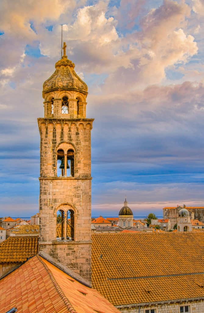 A view of the old Dominican Church and Monastery Bell Tower with Dubrovnik Cathedral and Bell Tower in the distance.