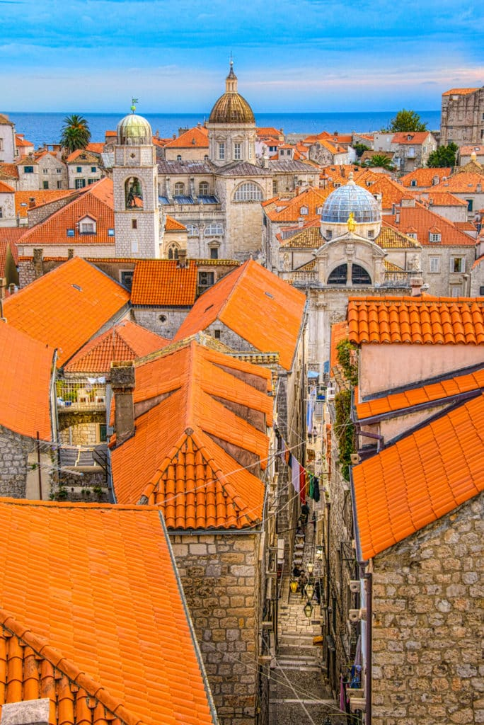 A view overlooking Dubrovnik Old Town's red-tiled roofs with the Church of St. Blaise, the Dubrovnik Clock Tower, and the Dubrovnik Cathedral in the distance.