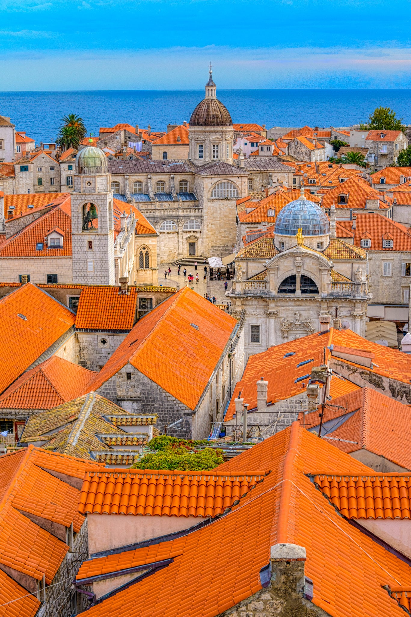 A view overlooking Dubrovnik Old Town's red-tiled roofs with the Church of St. Blaise, the Dubrovnik Clock Tower, the Dubrovnik Cathedral, and the Adriatic in the distance.