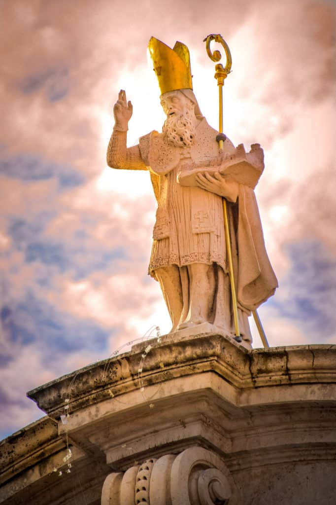 The statue of St. Blaise holding the City of Dubrovnik sits atop the Church of St. Blaise in Dubrovnik Old Town in Croatia.