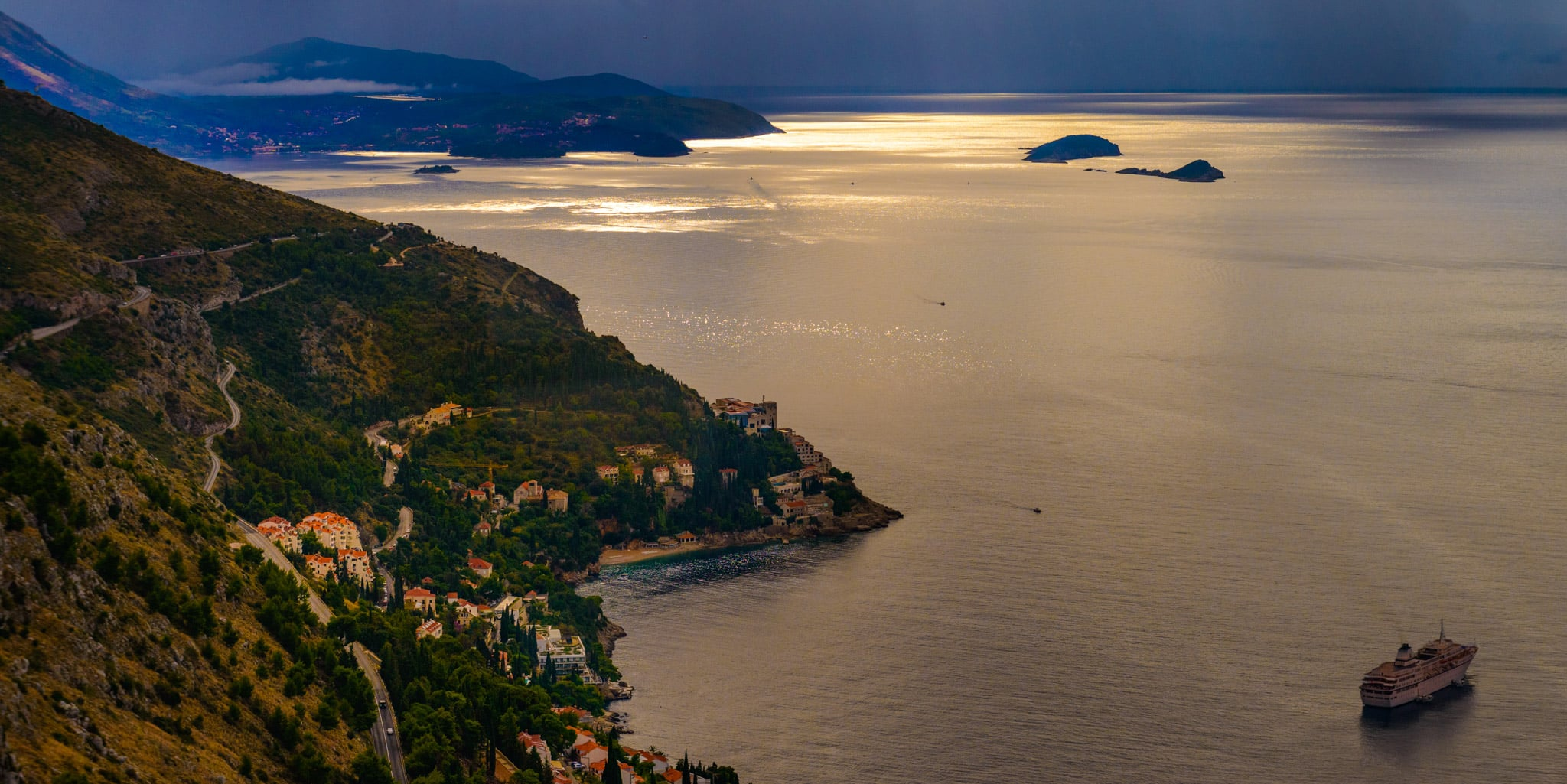 View of Dubrovnik harbor from Mt. Srdj with a winding road, beautiful villas, and a cruise ship.