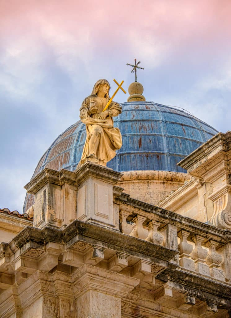 A personification of Faith sits atop a parapet on the Church of St. Blaise in Dubrovnik Old Town in Croatia.