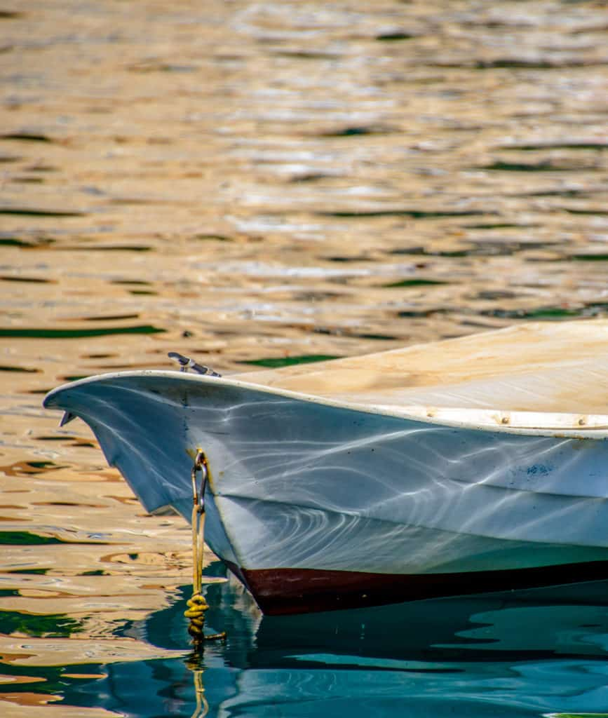 Sunlight reflecting off the water in the harbor of Dubrovnik Old Town adorns the bow of a moored rowboat.