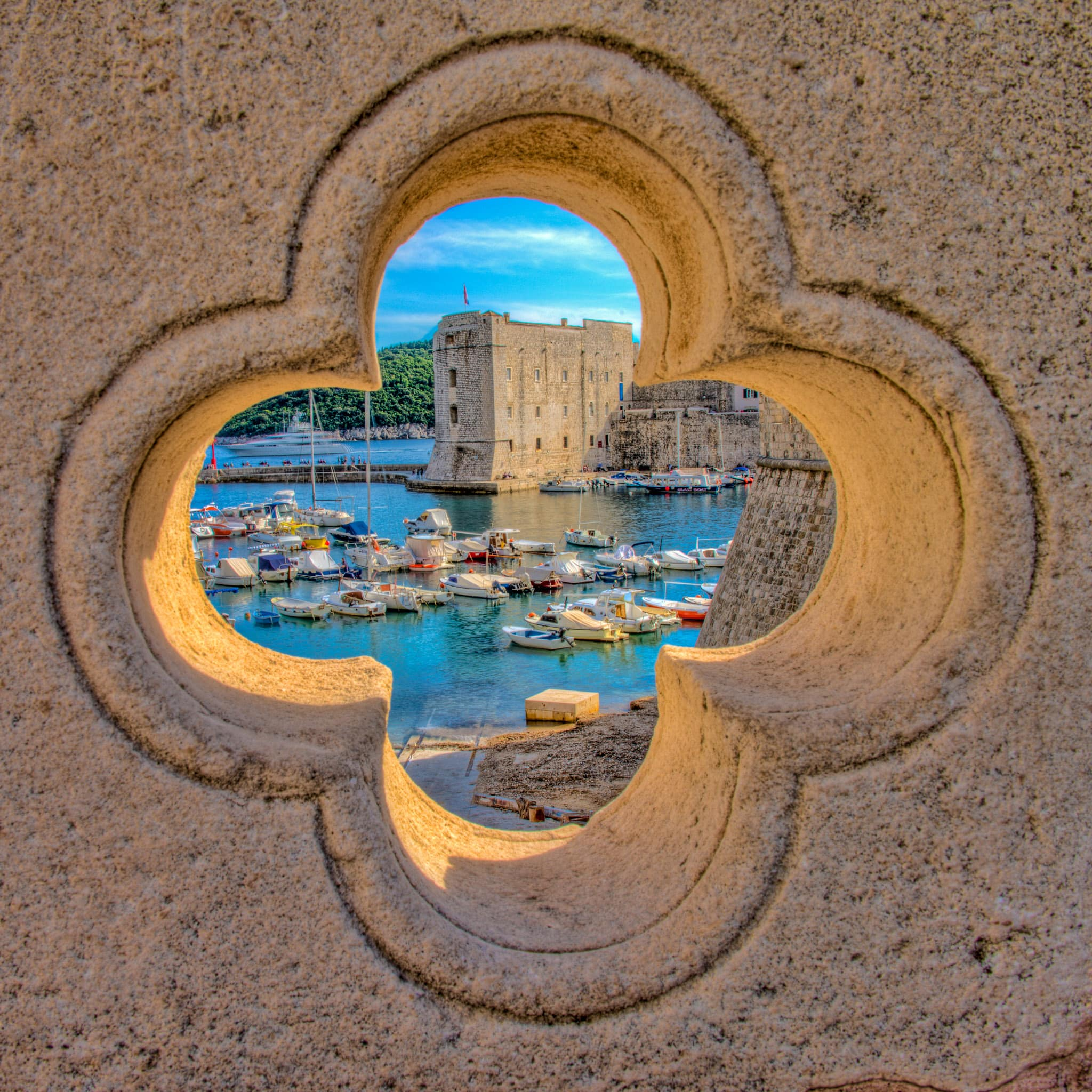 The harbor can be seen through one of many quatrefoils that adorn the bridge at the Ploce Gate in Dubrovnik Old Town in Croatia.