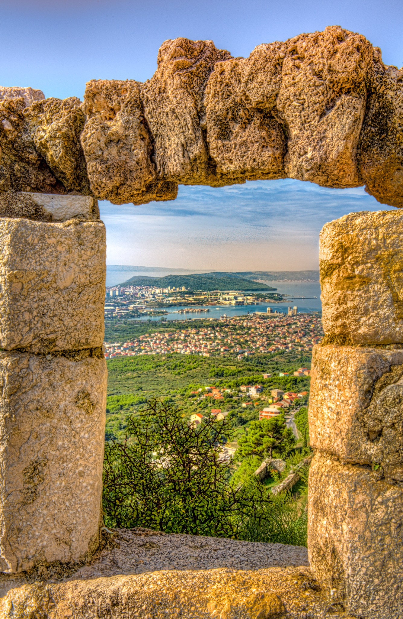 The Croatian city of Split is framed through an opening in the fortification walls of Klis Fortress.