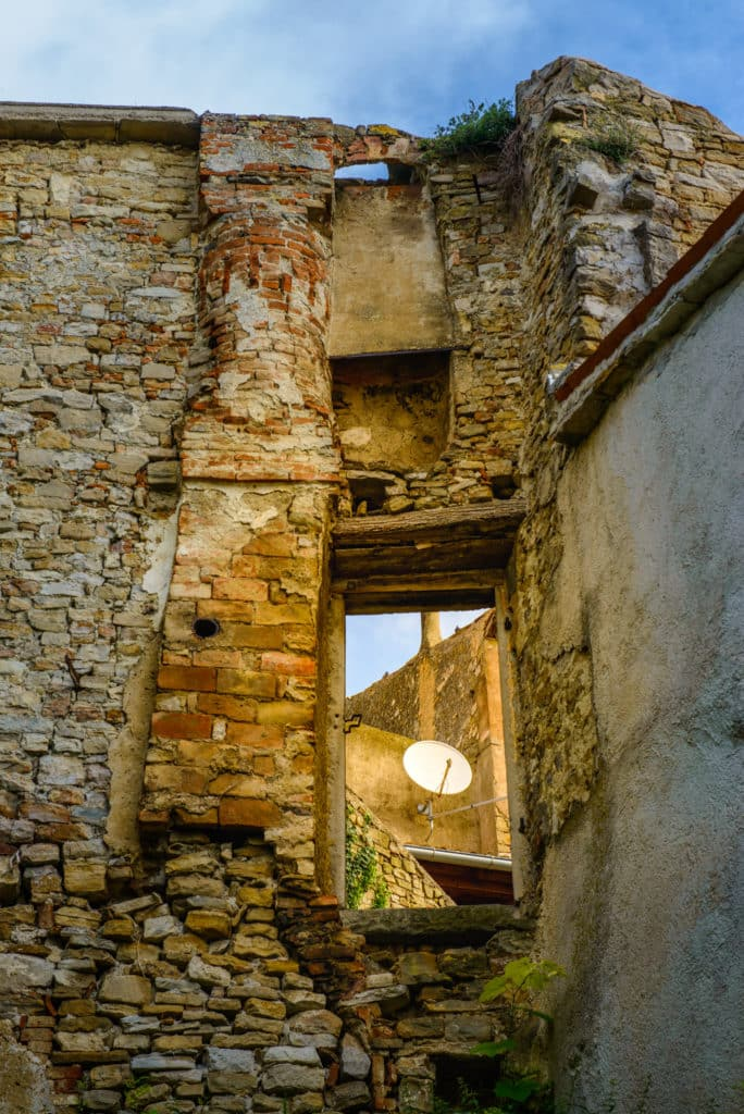 A satellite dish is visible through a window in some ruins in the Medieval Istrian village of Motovun in Croatia.