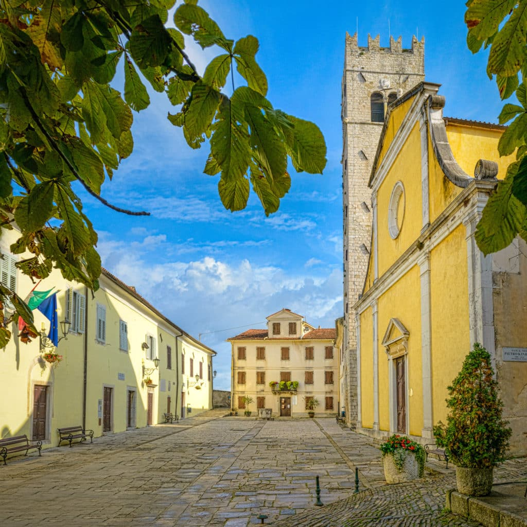 A view of the central square of the Medieval Istrian village of Motovun, Croatia, with the 13th Century bell tower, the Church of St. Stephen, and the Romanesque Municipal Palace.