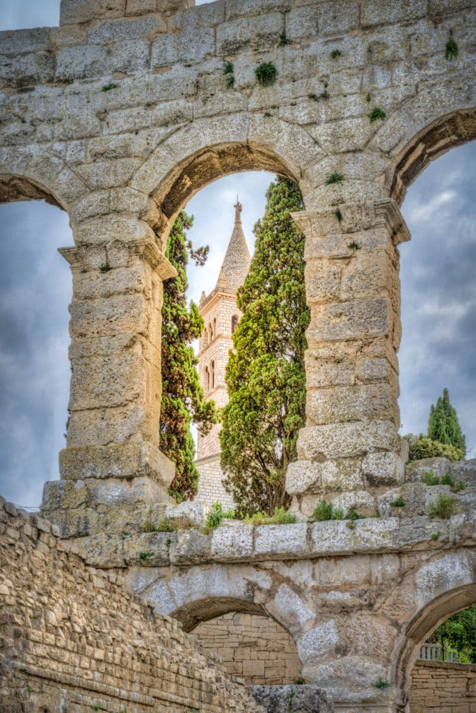 A view of the bell tower of the Church of St. Antun as seen through an upper arch in the wall of the Roman amphitheater in the Istrian city of Pula, Croatia.