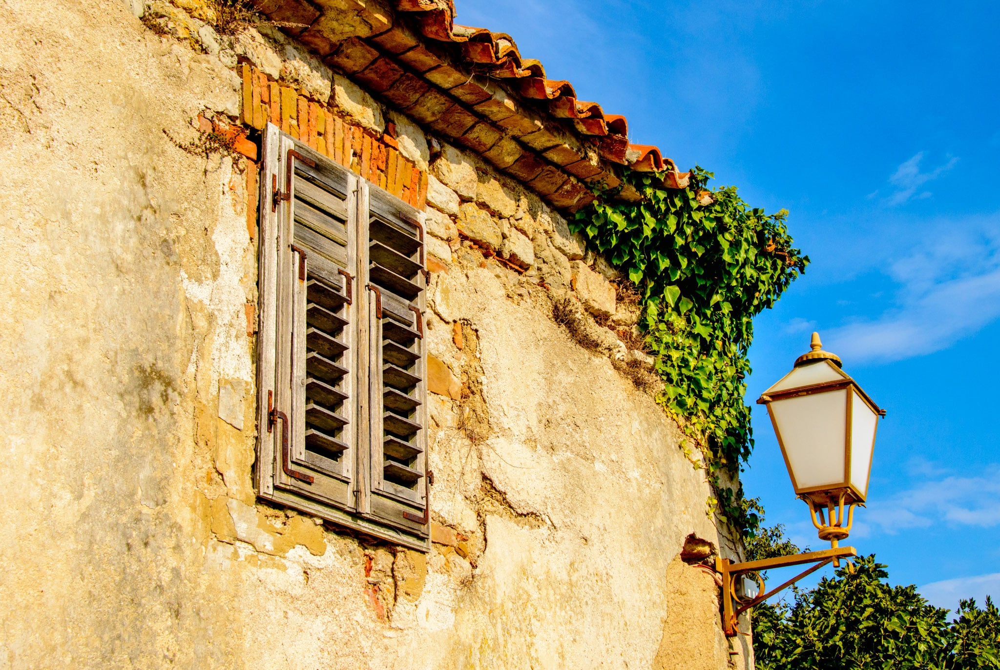 A street light and ivey adorn the ruined walls of a structure in Krk, Croatia.