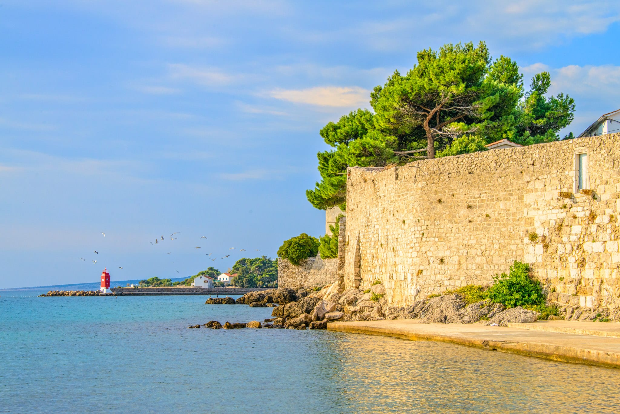 A view of the city walls and a lighthouse in Krk, Croatia.