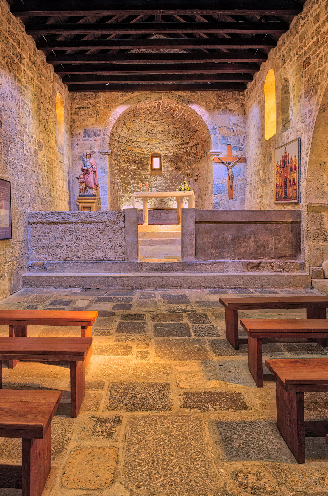 The interior of the Church of St. Lucy with a reproduction of the Baska Tablet set into the low wall separating the chancel from the nave.