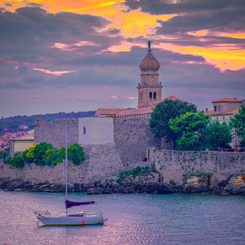 A sail boat sits at anchor near the medieval walls of Krk, Croatia, with Krk Cathedral in the distance.