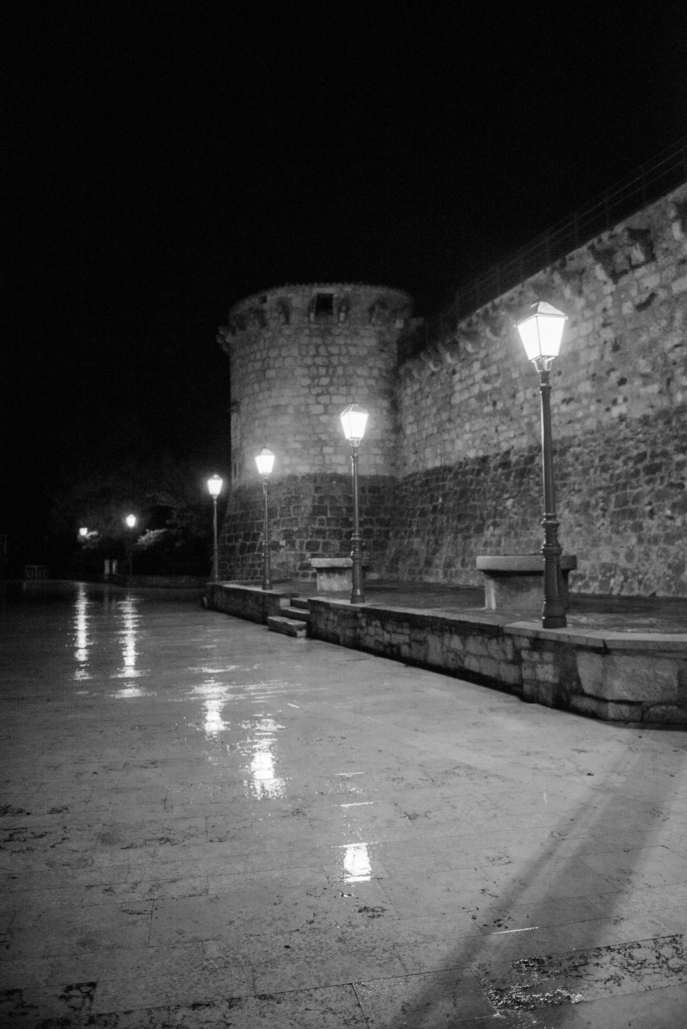 Street lights reflect in wet marble pavers along a wall of the Francopan Castle in Krk on the island of Krk in Croatia.
