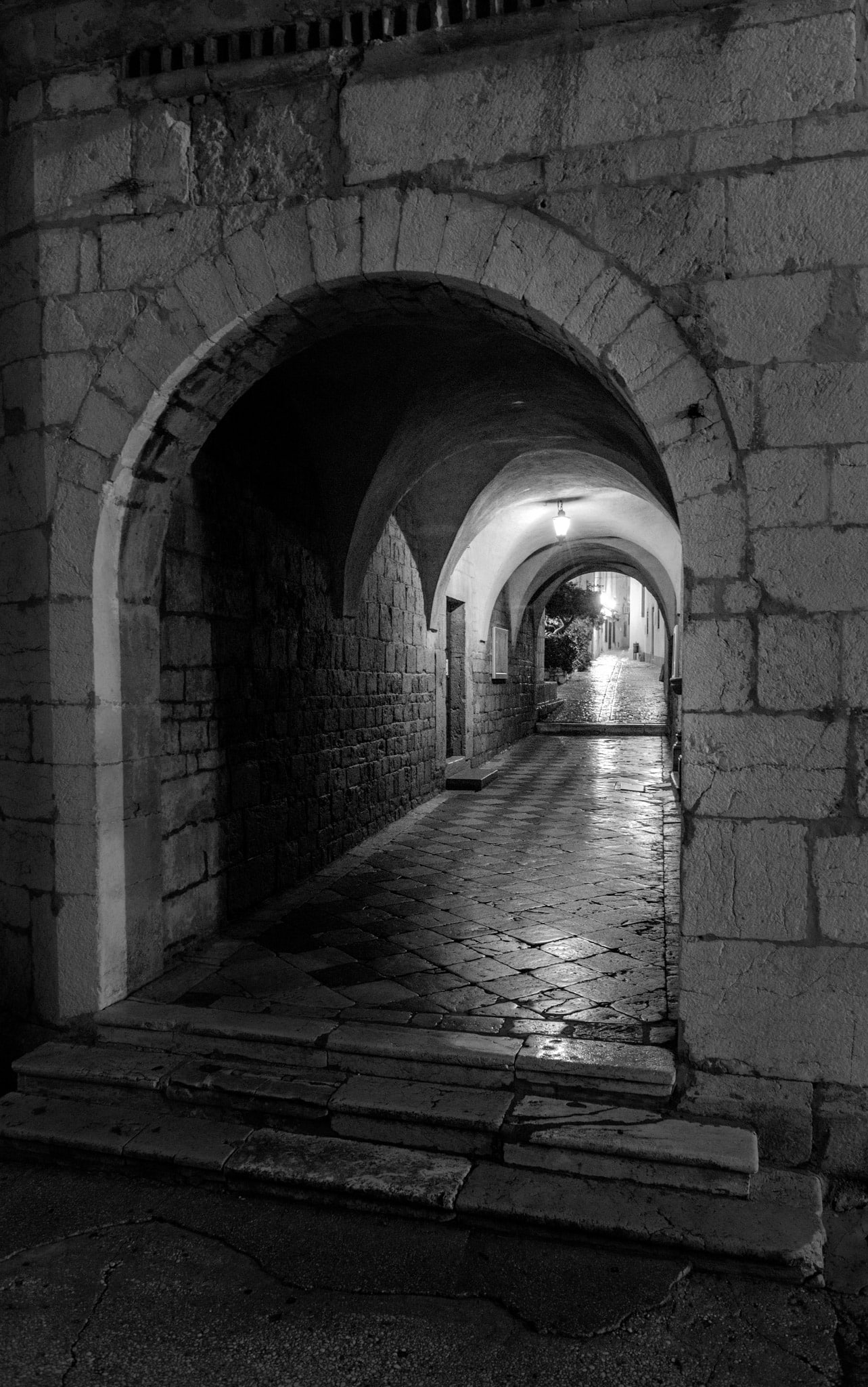 A nighttime view through a vaulted tunnel to an old cobbled street in the heart of Old Town Krk on the island of Krk in Croatia.