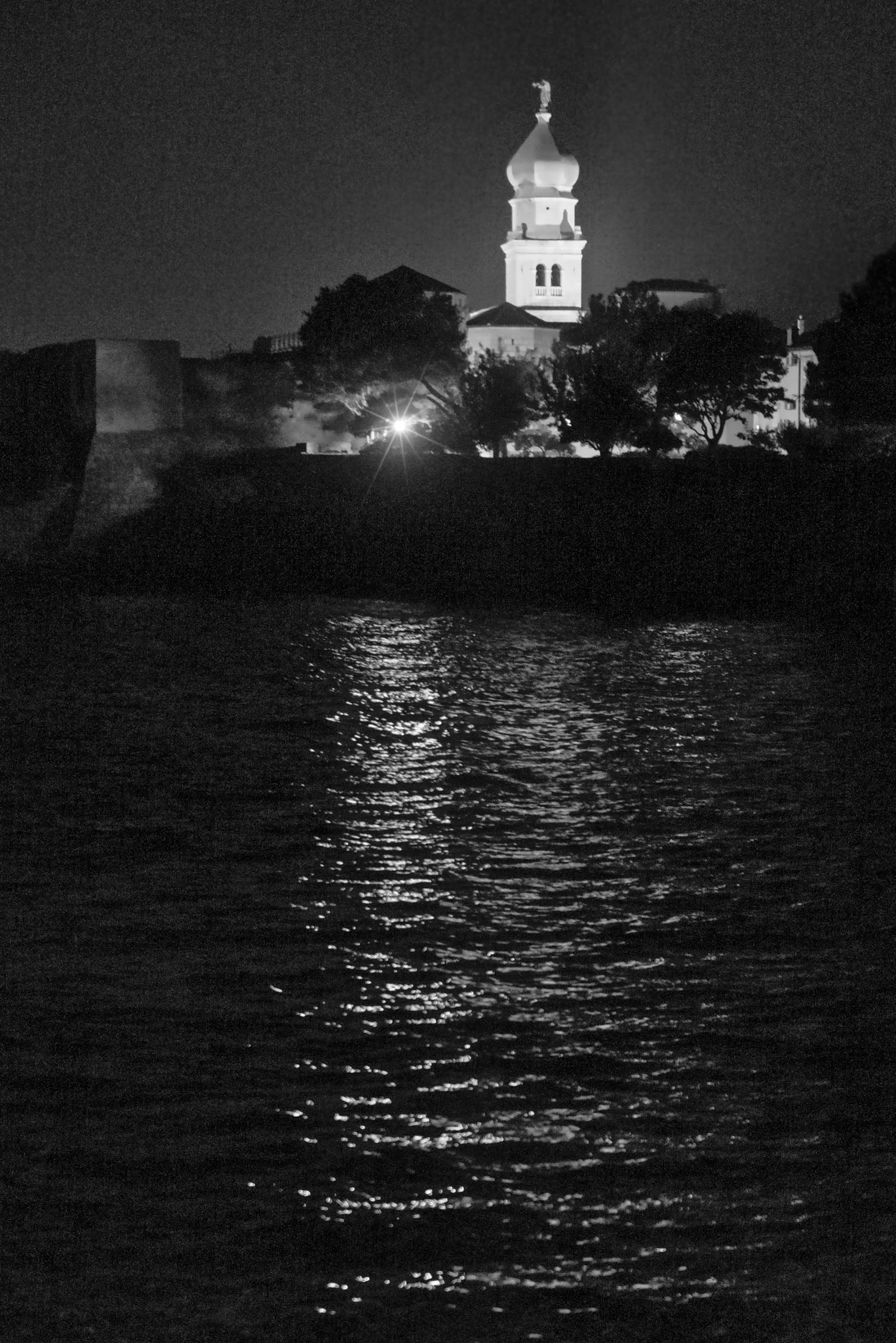 Krk Cathedral is illuminated at night and casts reflections in the harbor waters.