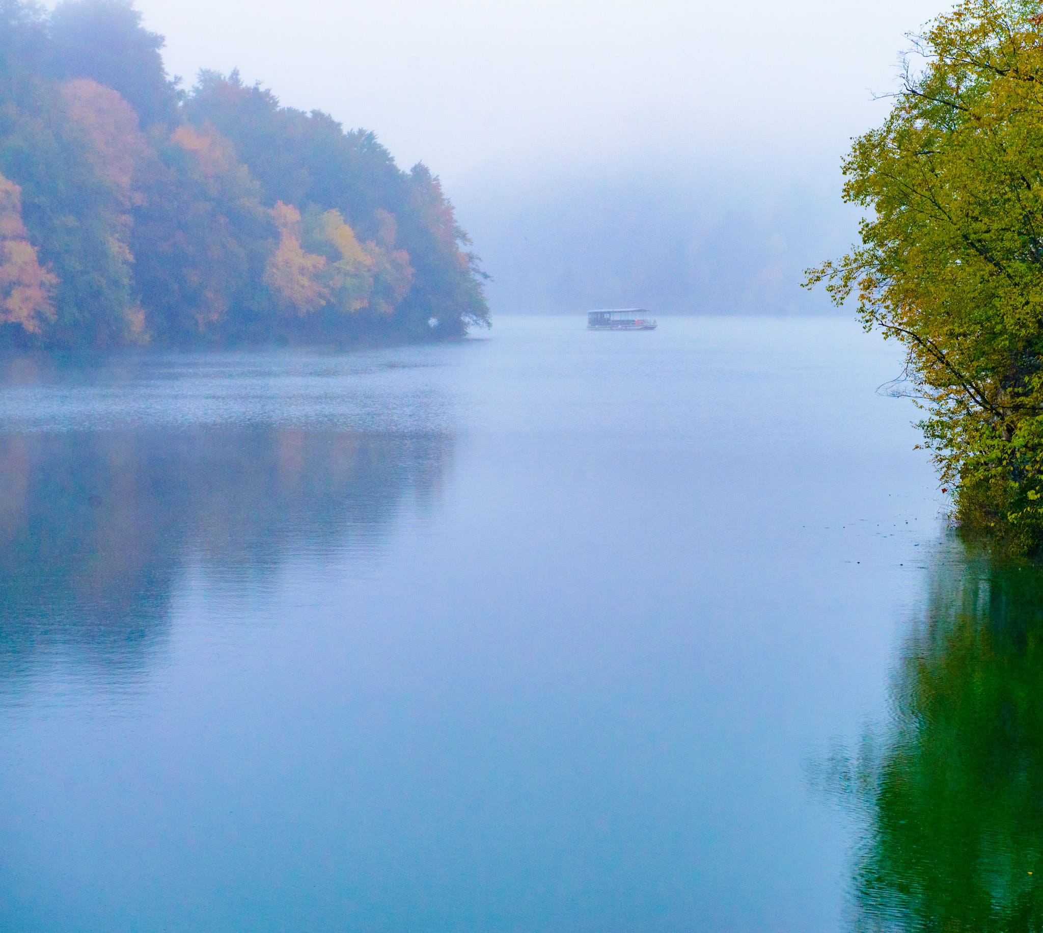 An electric ferry boat carries tourists through the fog on Lake Kozjak in Plitvice Lakes National Park in Croatia.