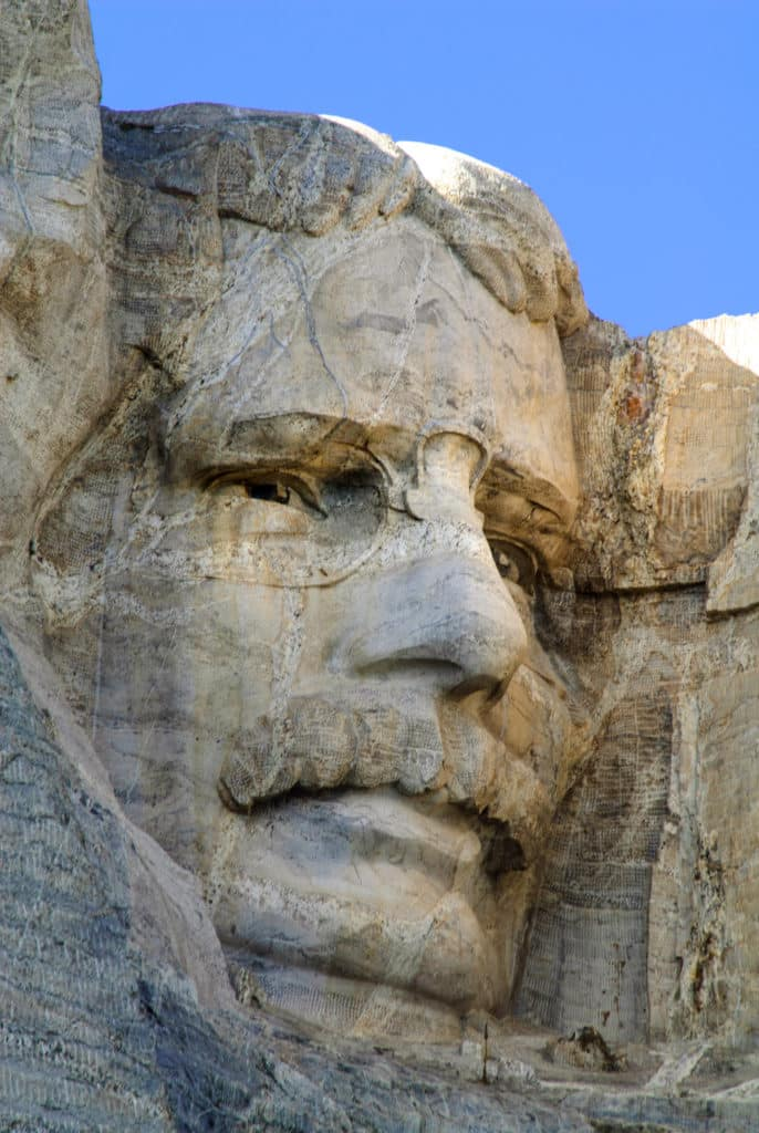 A close-up of the face of President Theodore Roosevelt carved into Mt. Rushmore.