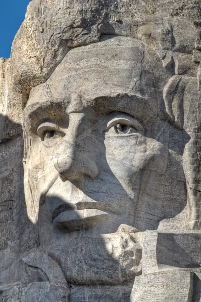 A close-up of the face of President Abraham Lincoln  carved into Mt. Rushmore.