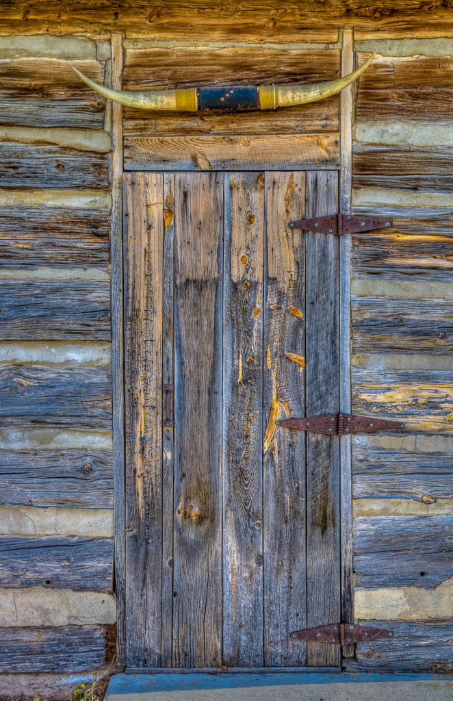 Steer horns are nailed above a plank door with rusty hinges on a cabin in Crawford, Nebraska.