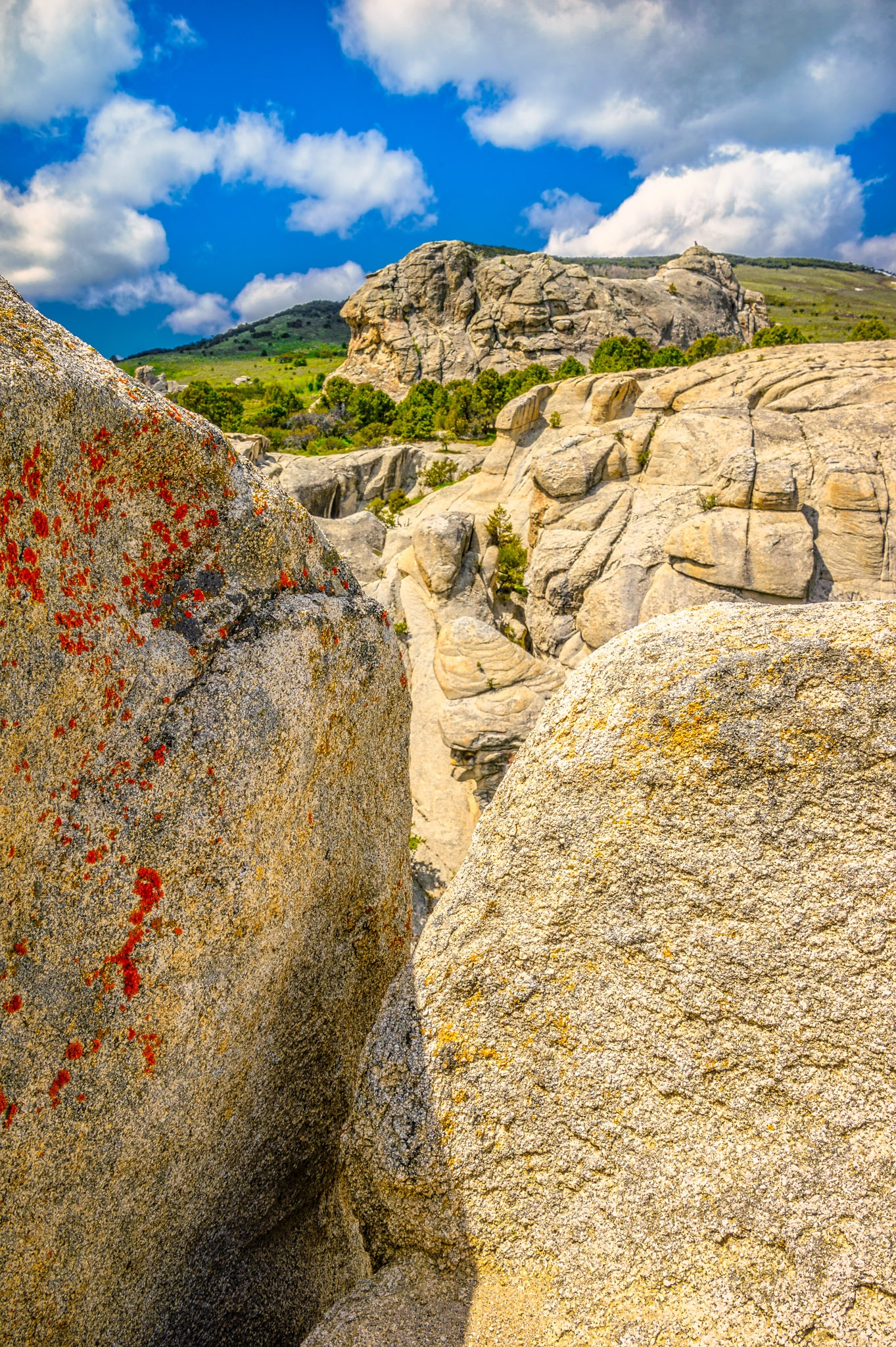 A view through a cleft in a granite rock showing additional granite formations in the distance in City of Rocks National Preserve, near Almo, Idaho.