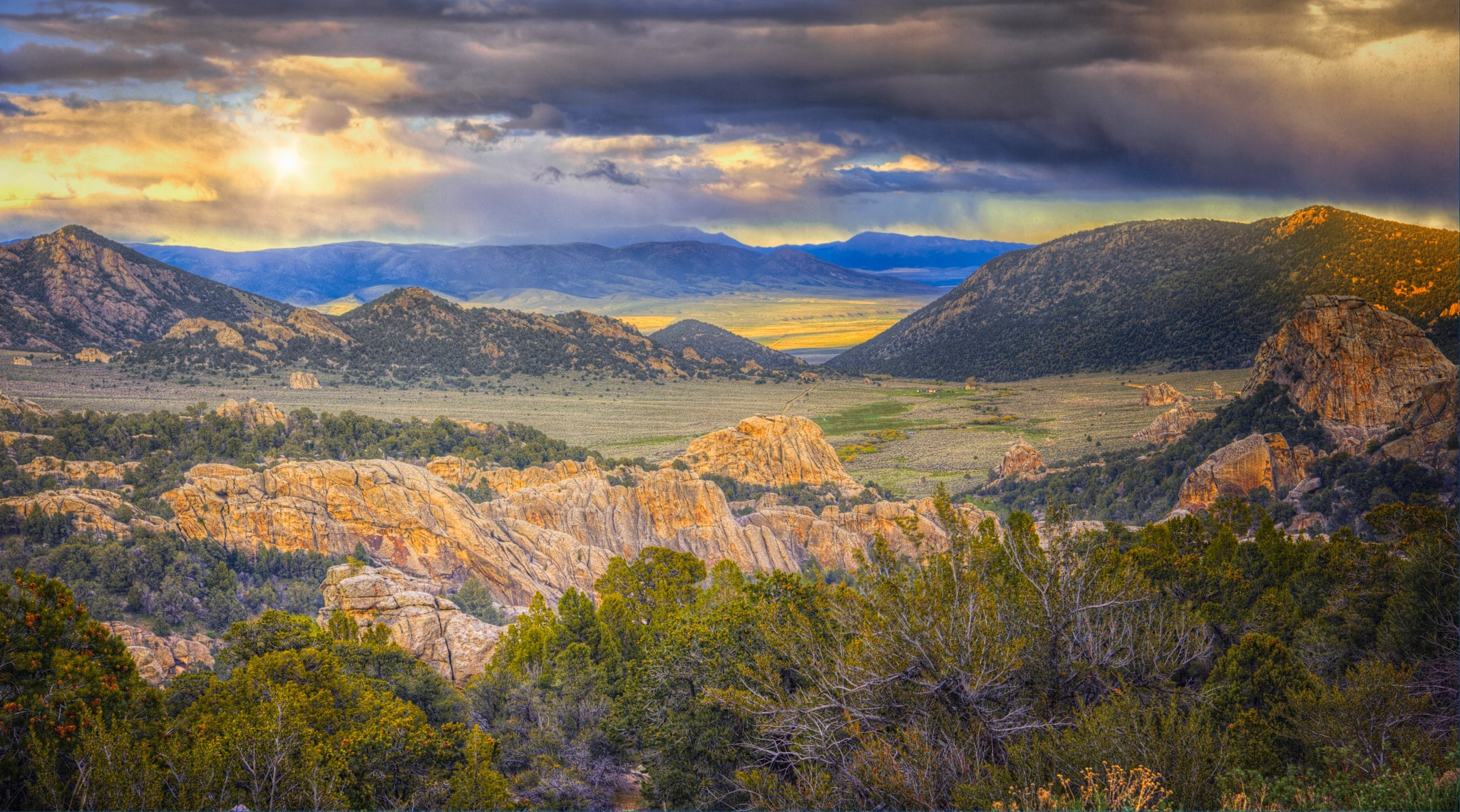 The sun shows through retreating snow clouds in City of Rocks National Reserve at sunset, near Almo, Idaho.