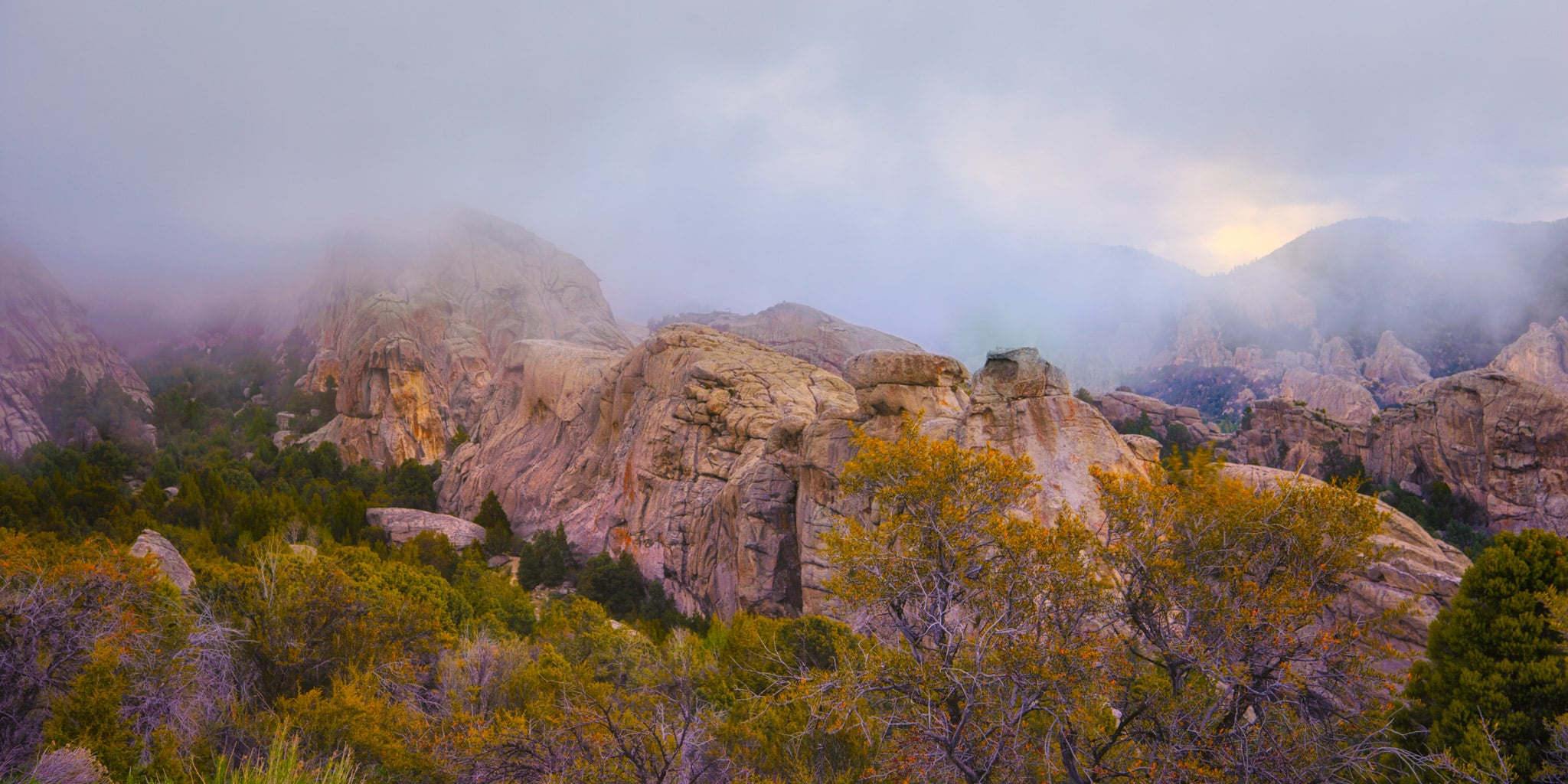 The sun peaks through retreating snow clouds in City of Rocks National Reserve at sunset, near Almo, Idaho.