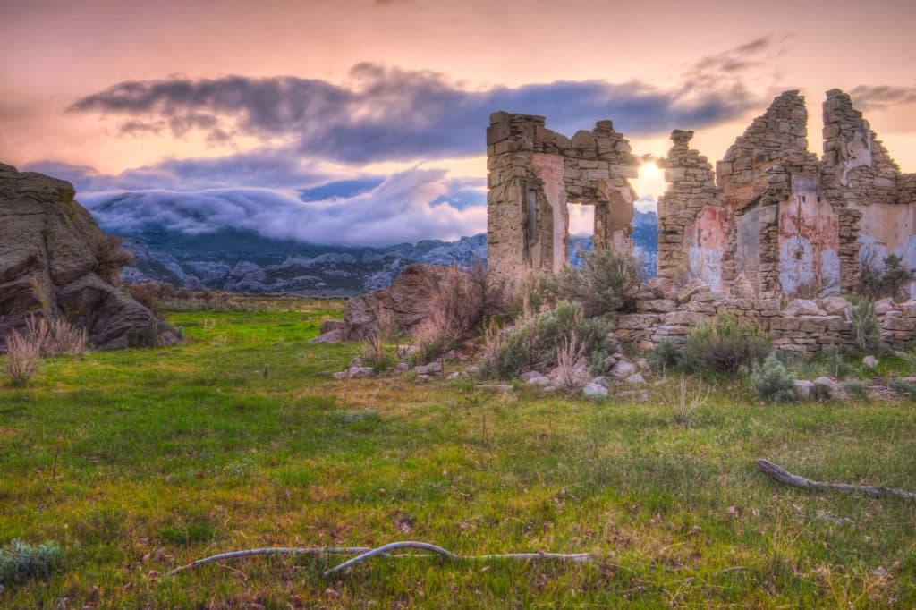 Clouds roll down the Albion Mountains at sunet with stone ruins in the foreground in City of Rocks National Reserve in Idaho.