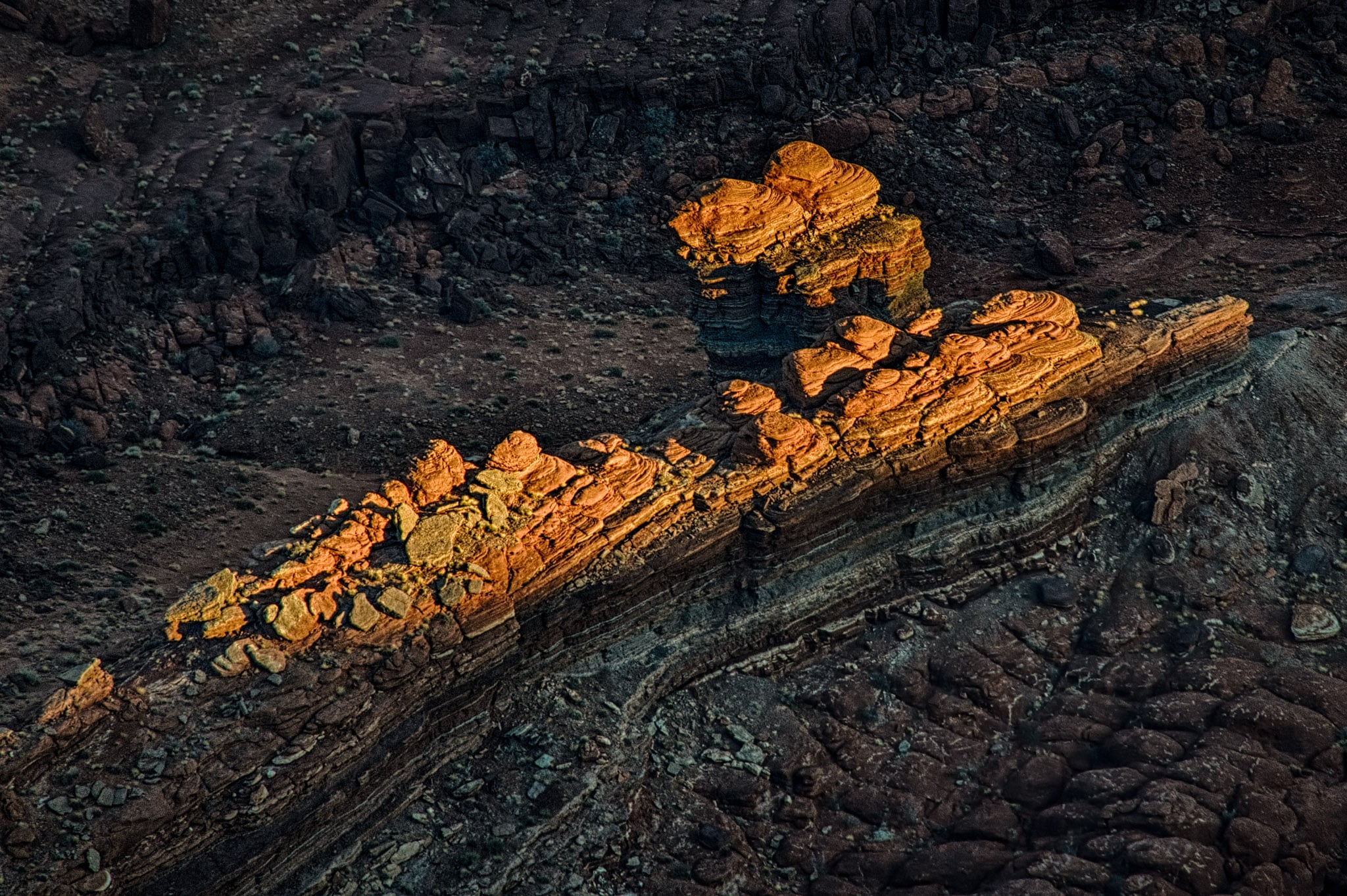 The last sunlight catches the tips of a butte below Dead Horse Point, near Moab Utah.
