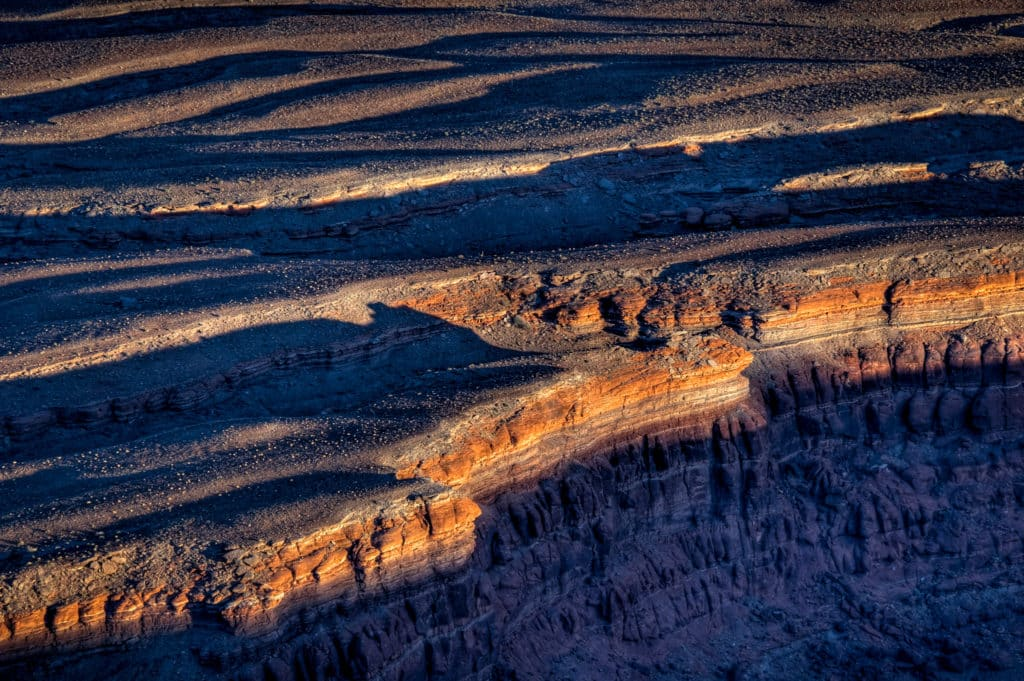 Sunset light catches the lip of the plateau below Dead Horse Point near Moab, Utah.