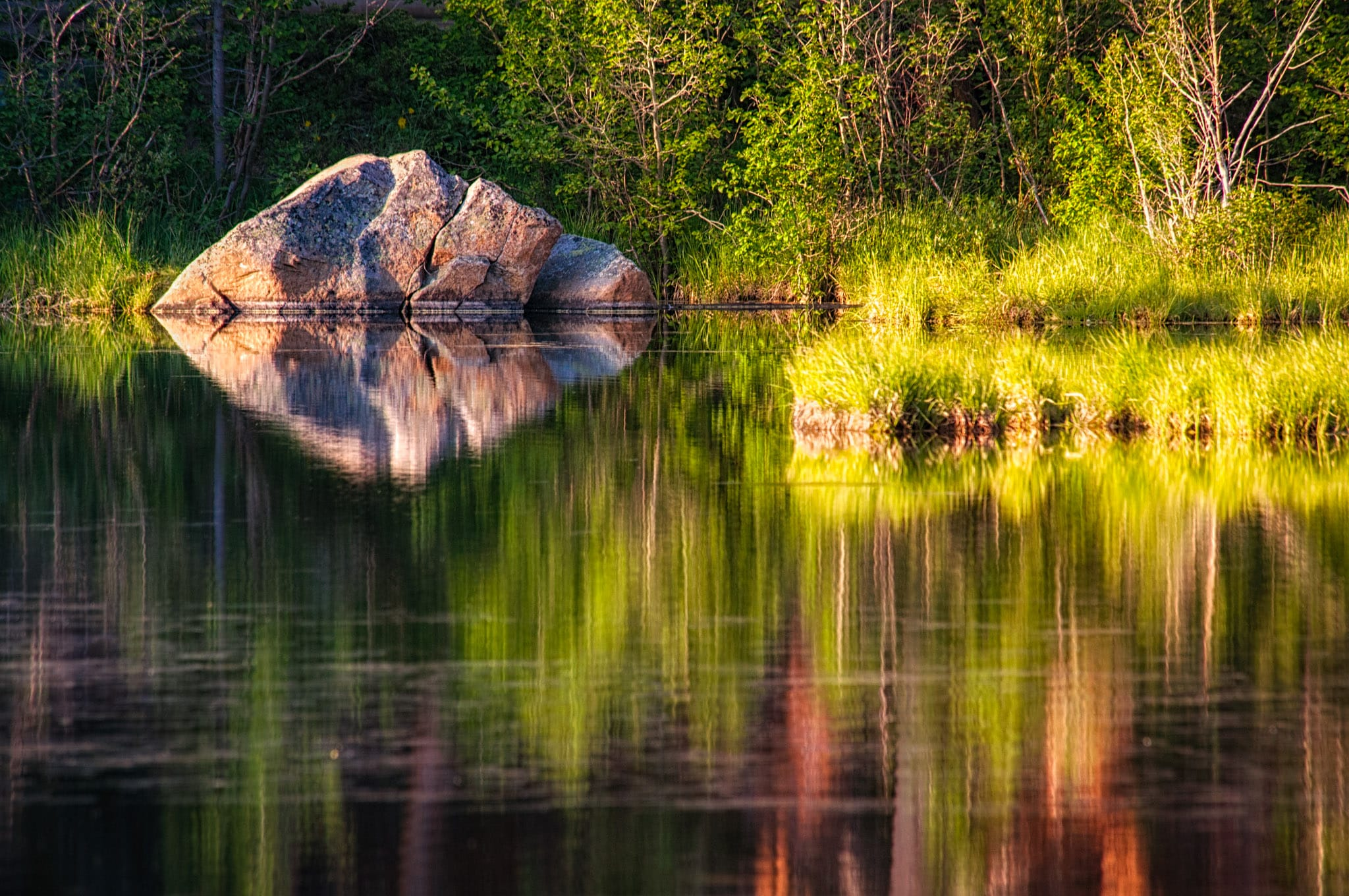Zen rock reflected in Sprague Lake in Rocky Mountain Park.