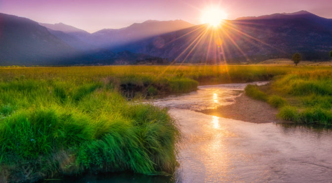 The sun dips behind Beaver Mountain as seen from the edge of Big Thompson River as it meanders through Moraine Park in Rocky Mountain National Park. - purchasing a fine art print