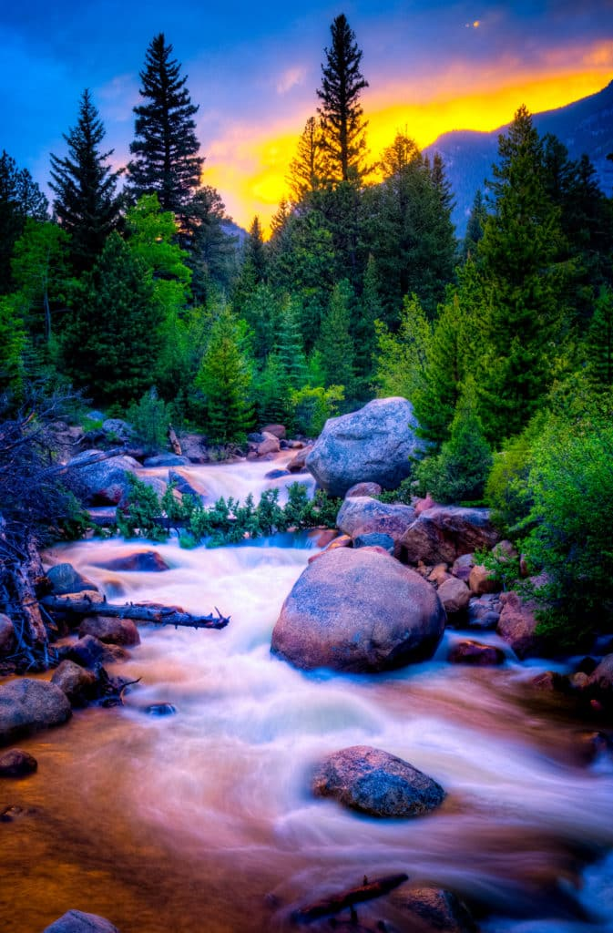 An early summer sunset makes Fall River glow near Aspenglen Campground in Rocky Mountain National Park, Colorado.