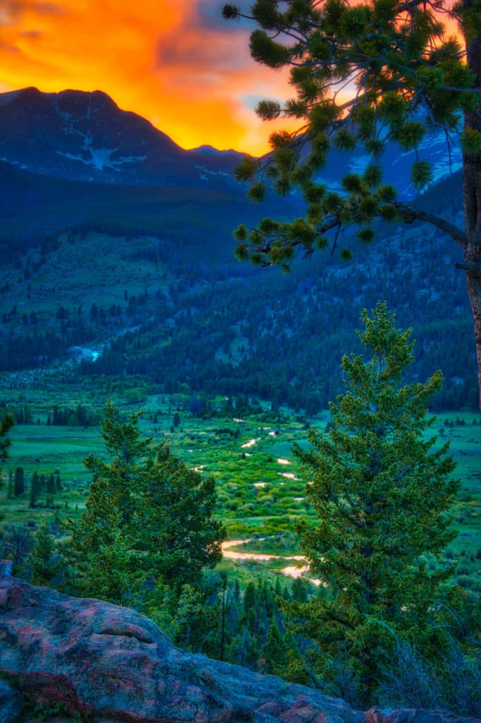 A meandering stream reflects the orange sunset from an overlook in Rocky Mountain National Park, Colorado.