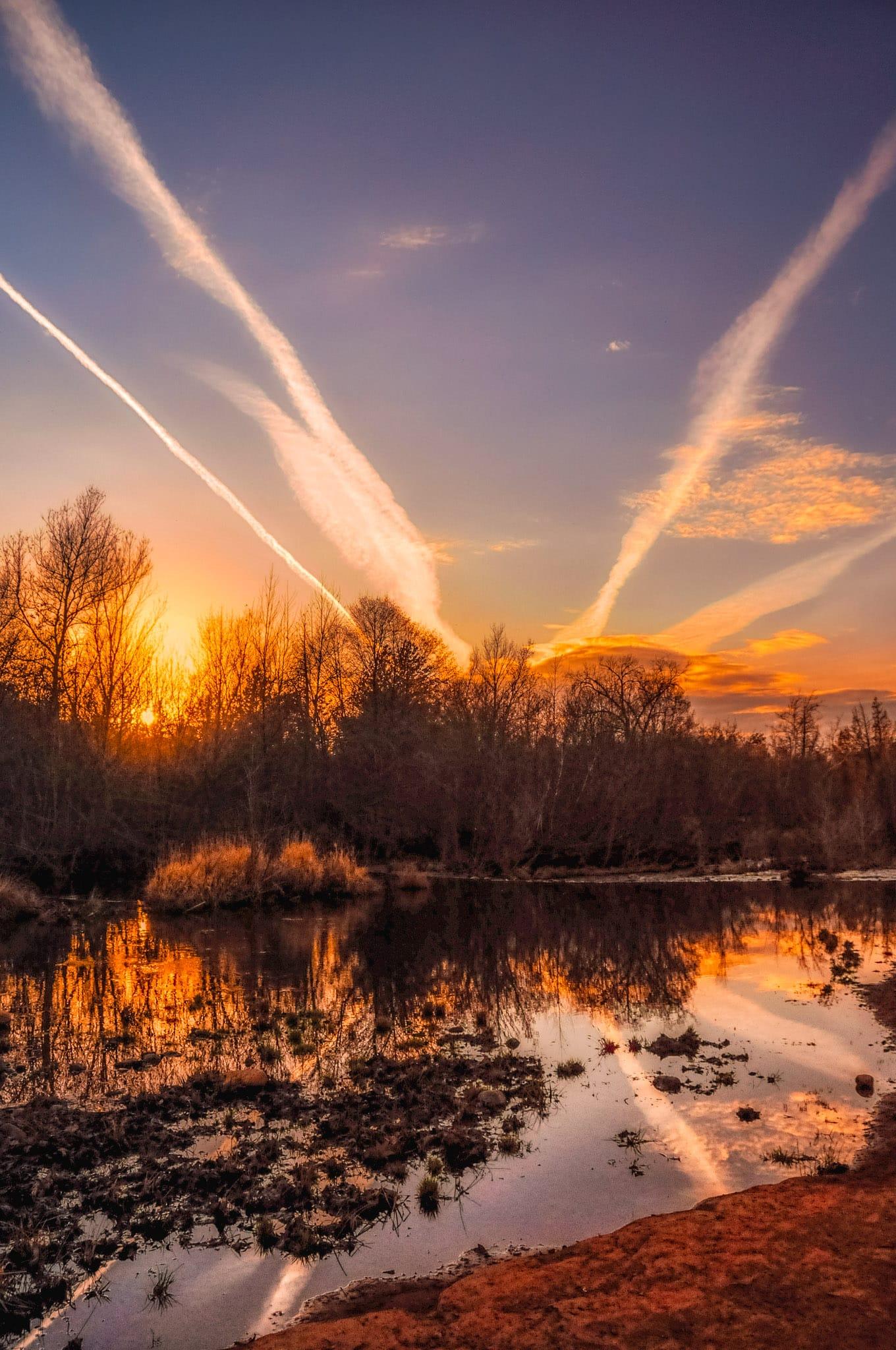 Contrails in sunset sky, reflected in Oak Creek near Red Rock Crossing in Sedona, Arizona.