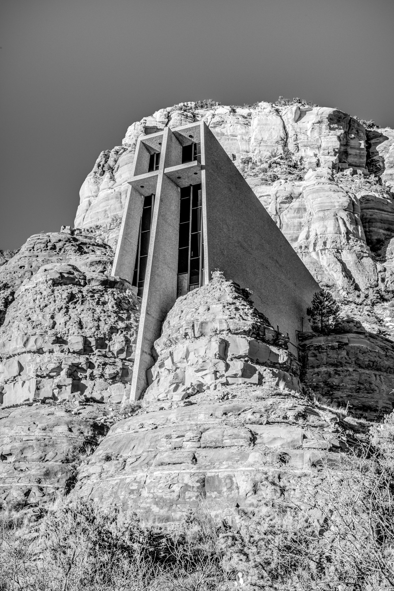 A black and white exterior view of the Chapel of the Holy Cross in Sedona, Arizona.