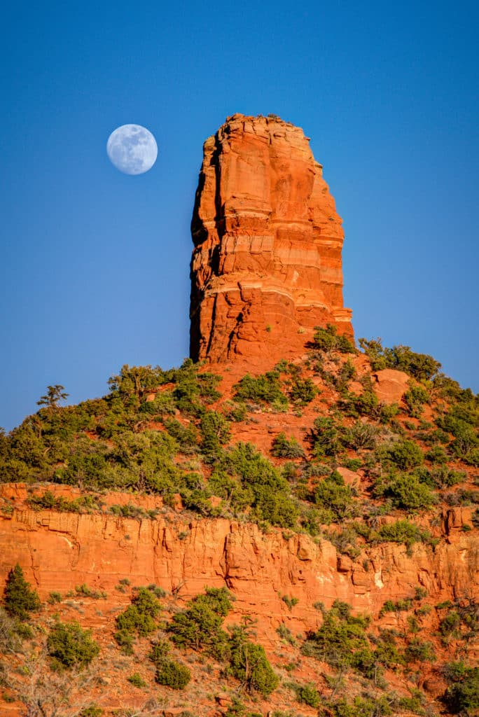 Moon rising over Chimney Rock as seen from Dry Creek Road in Sedona, Arizona.