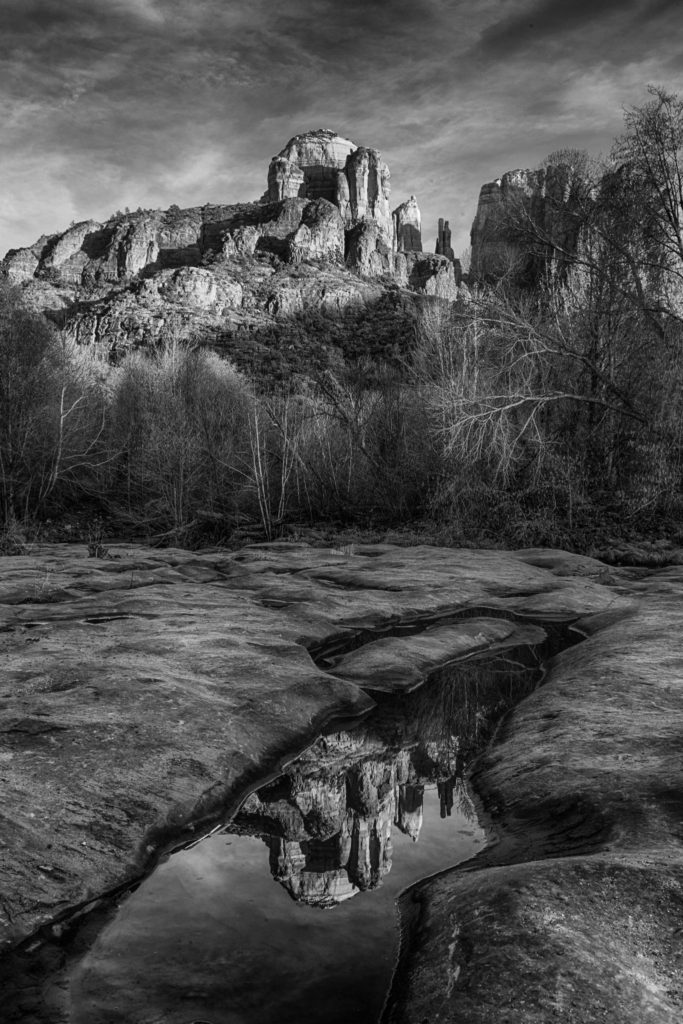 The classic view of Cathedral Rock reflected in the pot holes in Red Rock Crossing, along Oak Creek in Sedona, Arizona.