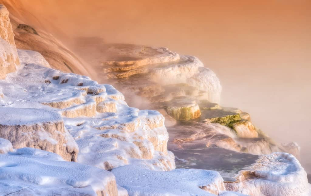 Water cascades over travertine terraces in the Mammoth Hot Springs area of Yellowstone National Park. The tracks in the snow are probably those of a coyote.