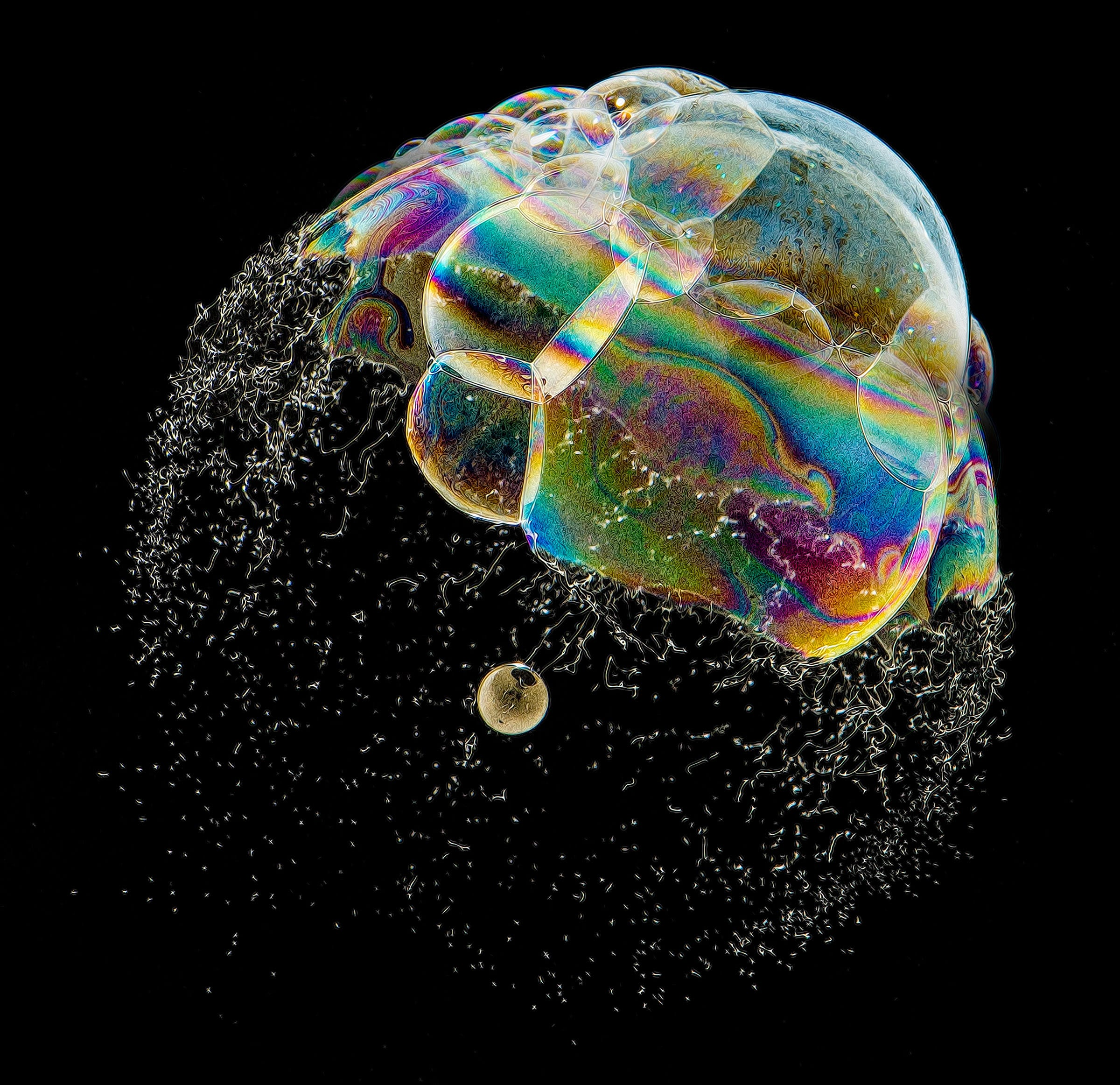 A colorful compound soap bubble in the process of bursting.
